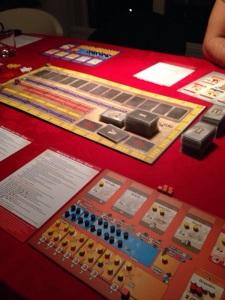Hovedbrettet i midten skal fylles med kort og har forskjellige skalaer til å vise inntekt til spillerne.